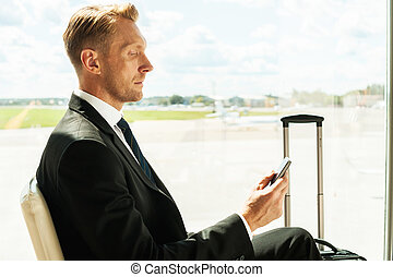 Businessman in airport. Side view of confident businessman in formalwear holding mobile phone while waiting for a flight in airport