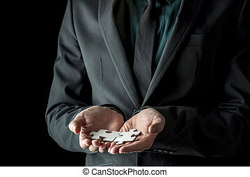 Businessman in black suit and tie holding two matching puzzle pieces