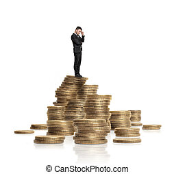 Businessman in black suit standing on heap of glittering golden coins isolated white background