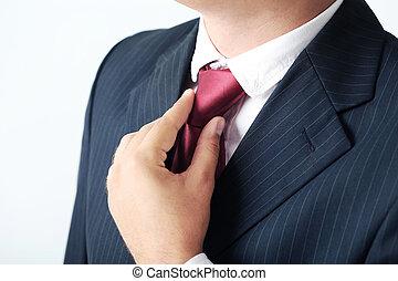 Businessman in black suit tying the necktie