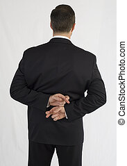 Businessman in black suit with two-handed finger cross behind back