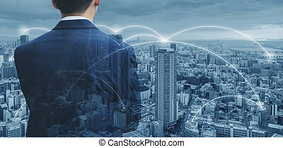 Businessman in blue suit looking at cityscape with network connection in the city. Business network technology, logistics and blockchain business
