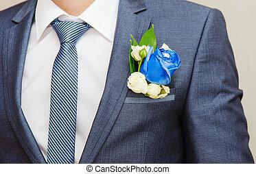 Businessman in blue suit tying the necktie