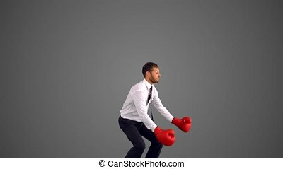 Businessman in boxing gloves jumping and punching on grey...