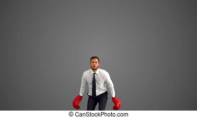 Businessman in boxing gloves leaping and punching his fists...