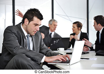 Businessman in business ambience working on laptop