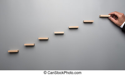Businessman in business suit building a graph or ladder of success