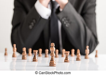 Businessman in business suit planning strategy with dark chess figures
