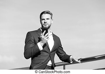 Businessman in business suit with mobile phone, new technology