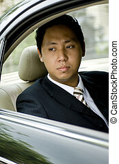Businessman In Car - A young asian businessman looks out of ...
