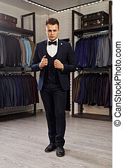 Businessman in classic vest against row of suits in shop. A young stylish man in a jacket. It is in the showroom, trying on clothes, posing. Advertising photo