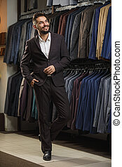 Businessman in classic vest against row of suits in shop
