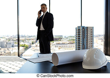 Businessman in construction company office, model of modern...