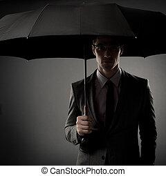 Businessman in costume holding black umbrella