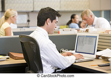 Businessman in cubicle using laptop
