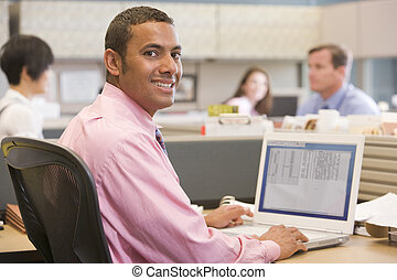 Businessman in cubicle with laptop smiling