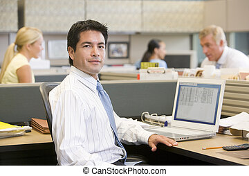 Businessman in cubicle with laptop