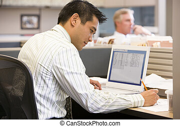 Businessman in cubicle with laptop writing