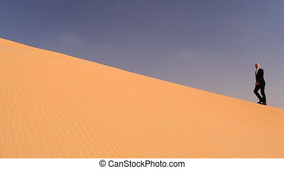 businessman in desert sand - businessman climbing a dune in...