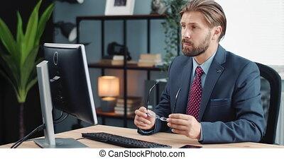 Businessman in eyeglasses looking at computer screen - ...
