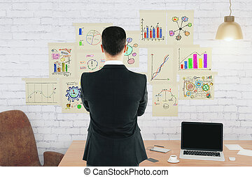 Businessman in front of brick wall with business scheme concept posters