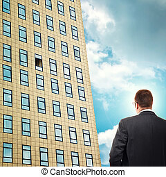 Businessman in front of company building.