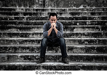 Businessman in frustrated depression sitting on the stairs, in scary abandoned building. The concept of unemployed, sadness, depressed and human problems in dark tone.