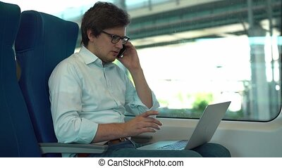 Businessman in glasses talking on phone and using laptop in a train