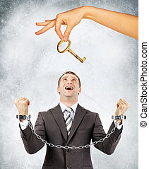 Businessman in handcuffs and big hand offering key