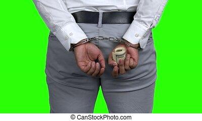 Businessman in handcuffs holding money, back view. Handcuffs...
