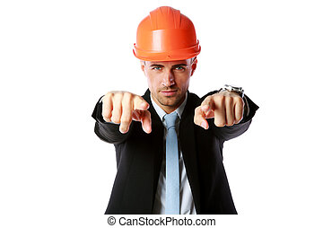 Businessman in hard hat pointing at you over white...