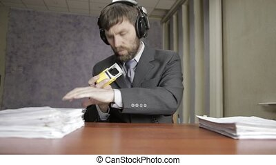 Businessman in headphones funy signing and stamping incoming documents.