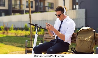 businessman in headphones playing game on cell - business,...