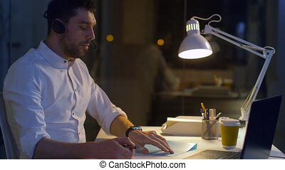businessman in headset with laptop at night office -...