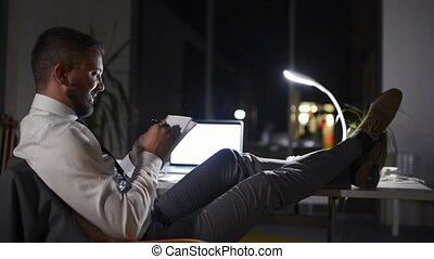 Businessman in his office at night working late.