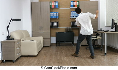 Businessman in his office is dancing after long hours of...