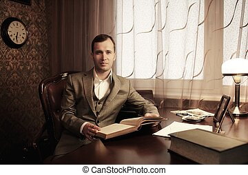 Businessman in home interior with a book