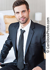 Businessman in hotel room. Confident young businessman in formalwear looking at camera and smiling while sitting on the bed in hotel room