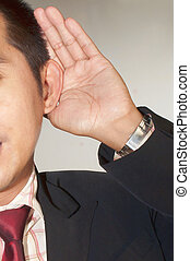 Businessman in listening pose - Businessman holding hand to...