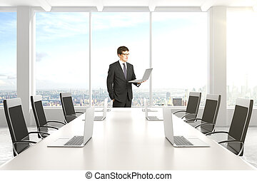 Businessman in modern conference room with furniture, laptops and big windows with city view