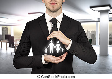 businessman in modern office protecting family papercut