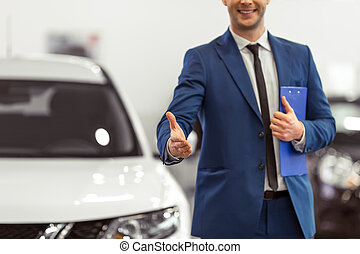 Handsome young man in classic blue suit is smiling and offering hand while standing near the car in a motor show, cropped