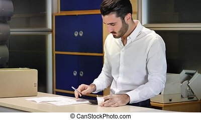 Businessman in office drinking coffee while working
