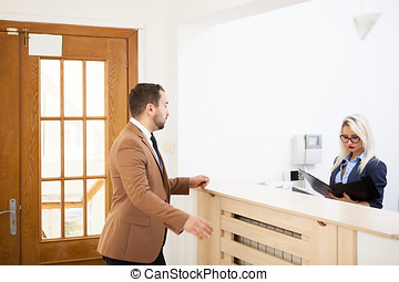 Businessman in office reception area talking with secretary