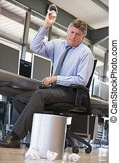 Businessman in office space throwing garbage in bin