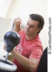 Businessman in office using small punching bag to relieve stress