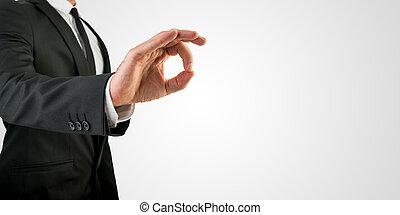 Businessman in OK Hand Sign on Grey Background