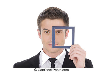Businessman in picture frame. Confident young man in formalwear looking through a little picture frame while isolated on white