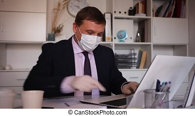 Businessman in protective mask working alone with laptop and papers in office
