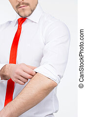 Businessman in red necktie. Cropped image of bossy young man adjusting his shirt while standing isolated on white
